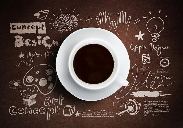 Close up of cup of coffee on table with sketches on background-min