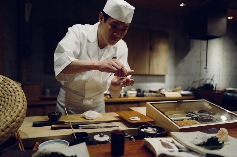 Seorang chef yang sekaligus pemilik binis kuliner ini sedang membuat sushi.