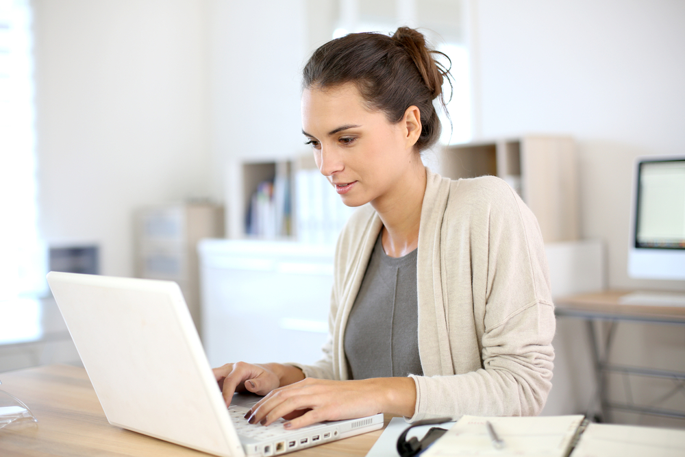 Attractive woman working in office on laptop - freelance writer - Bisnis Rumahan Modal Kecil