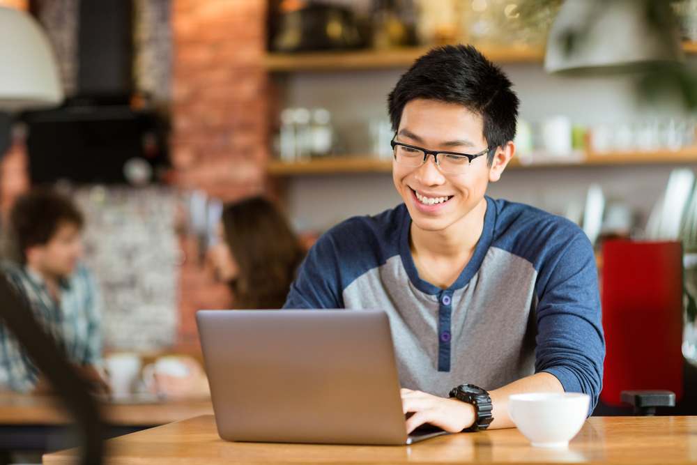 Happy cheerful young asian male in glasses smiling and using laptop in cafe - mudahnya komunikasi dengan pelanggan lewat aplikasi multiplechat