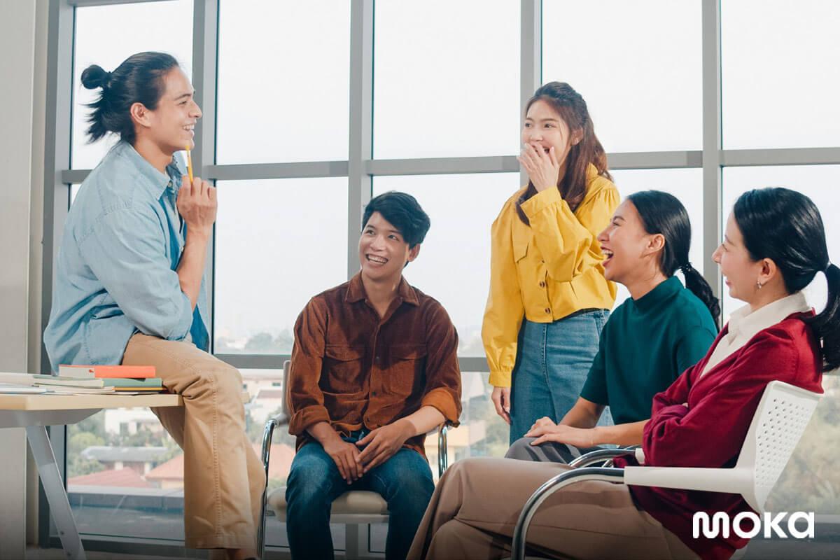 karyawan muda sedang brainstorming atau meeting - generasi milenial - tampak senang dengan kantor