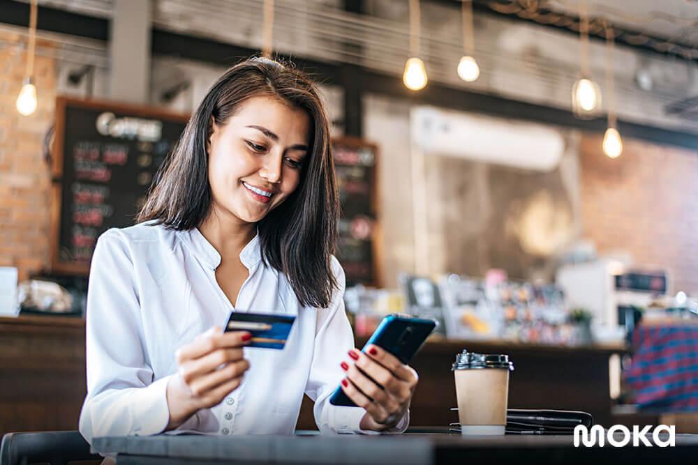 menggunakan kartu kredit atau debit untuk membayar belanjaan