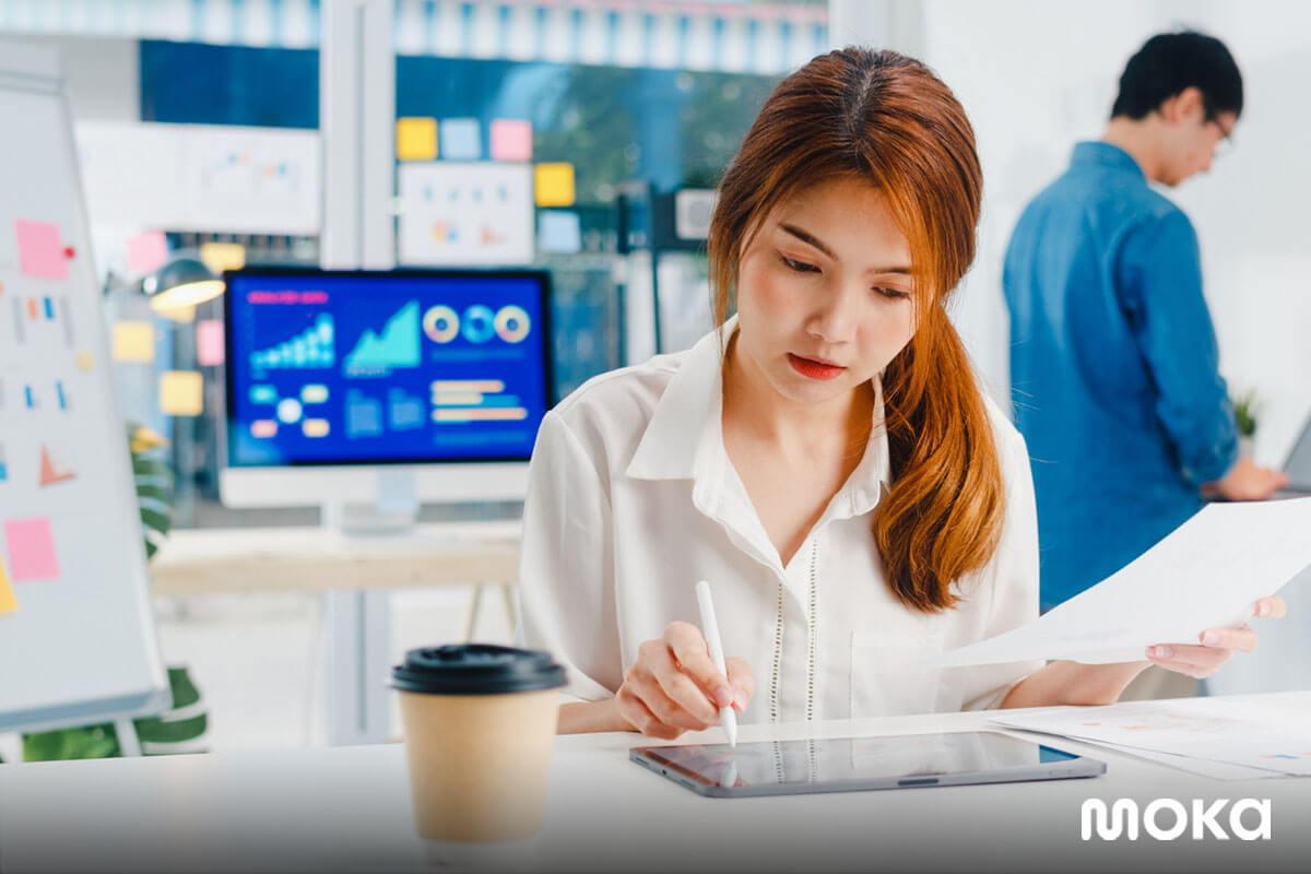pebisnis wanita sedang mengecek laporan penjualan usahanya (1)