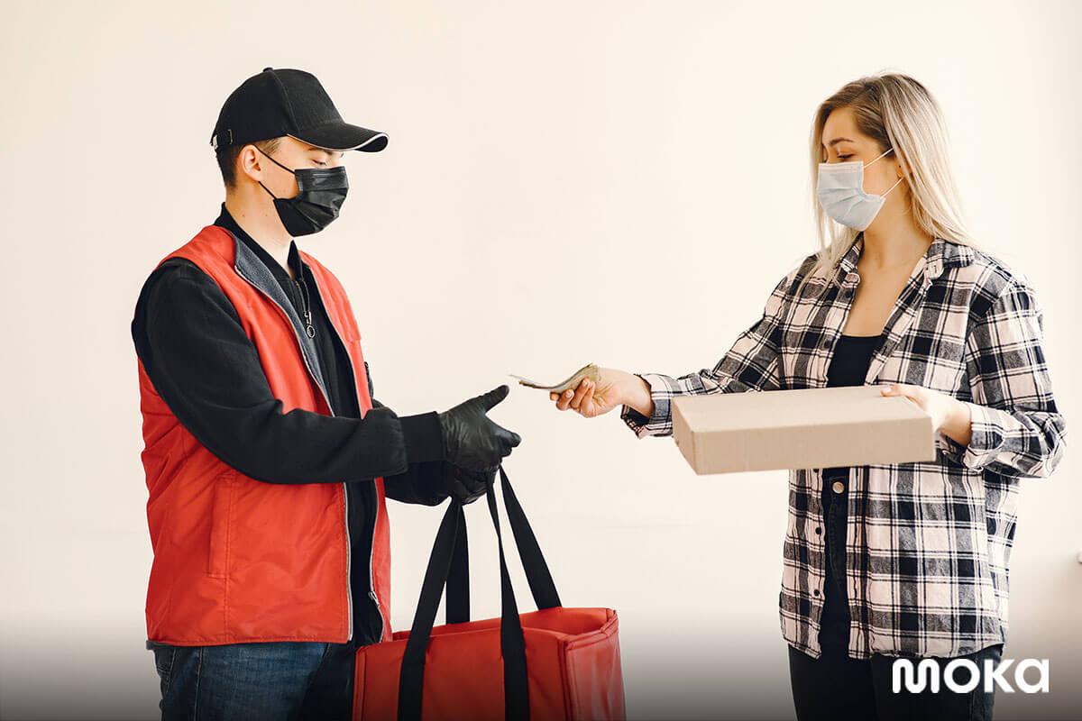 pelanggan menggunakan masker ketika mengambil online delivery dari gofood