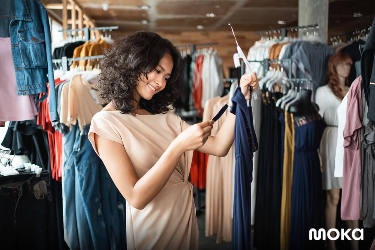 pelanggan sedang  melihat pakaian di toko retail